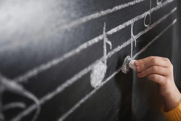 Child writing music notes on blackboard, closeup