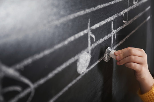 Child writing music notes on blackboard, closeup