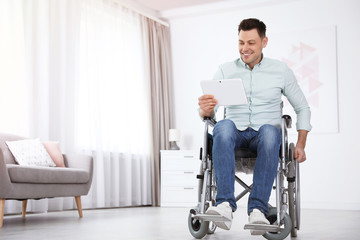 Happy man with tablet sitting in wheelchair at home