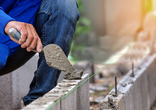Worker is cementing bricks with cement for brick in construction site