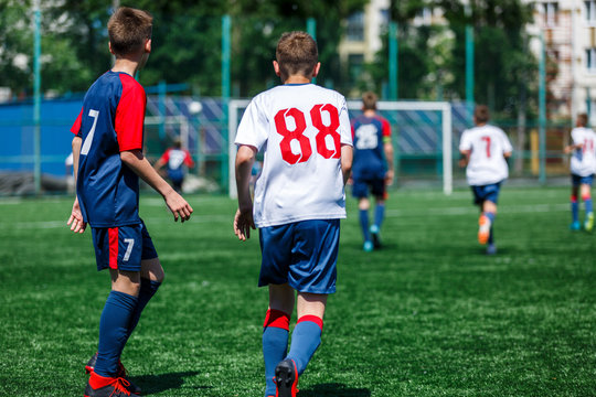 Boys in white and blue sportswear plays  football on field, dribbles ball. Young soccer players with ball on green grass. Training, football, active lifestyle for kids concept