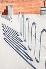 Modern curvy bike rack and shadows on concrete, cement sidewalk, abstact, background.