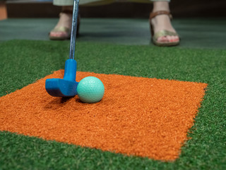 Blue putter on turf lined up next to green golf ball on miniature golf course with woman playing