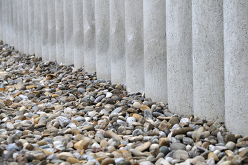 pebbles beside a wall of concrete posts