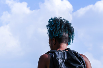 Rear view of young African man with backpack stand and blue sky background. Traveler concept.