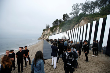 People gather around the runway before the Saint Laurent Men's Spring/Summer 2020 fashion show at Paradise Cove beach in Malibu