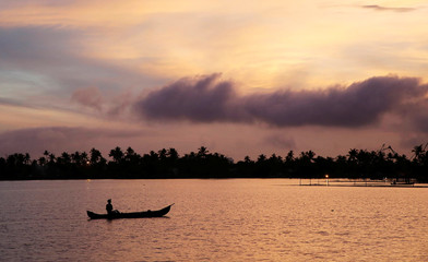 A man rows his boat in the tributary waters of Vembanad Lake against the backdrop of pre-monsoon clouds on the outskirts of Kochi