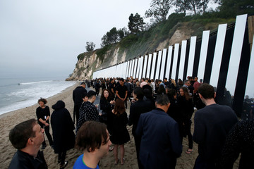 People gather near the runway before the Saint Laurent Men's Spring/Summer 2020 fashion show at Paradise Cove beach in Malibu