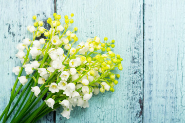 bunch of lily of the valley flowers on faded blue table, directly above