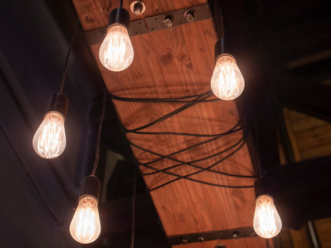 Vintage Victorian Light Bulb Quad Loop Filament Amber Tinted Hanging From Ceiling in Bar Restaurant or Speakeasy