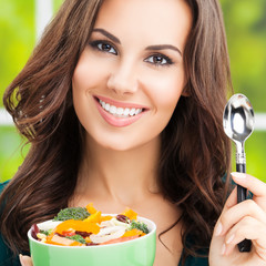 Portrait photo of cheerful smiling woman with salad, outdoors