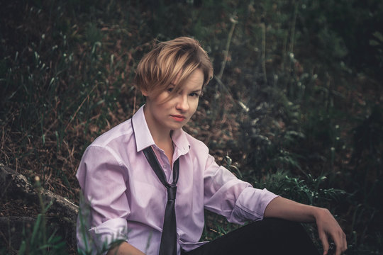 A beautiful and stylish woman with a slightly androgynous appearance with short blond hair (haircut), in a men's white shirt, black pants and tie, sits on the steps among the grass