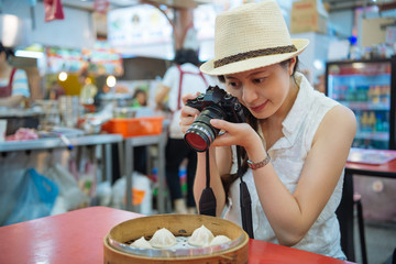 japanese girl traveler favorite taiwanese food Xiao Long Bao in bamboo steamer box. young asian woman photogrpaher taking picture from camera with pork dumpling sitting in local vendor eating smiling