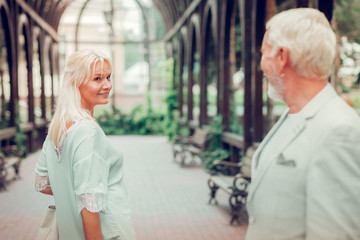 Joyful aged woman smiling to her man