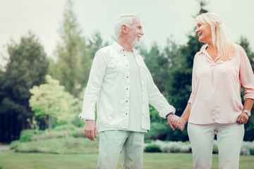Delighted cheerful man holding his wifes hand