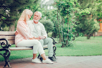 Positive aged couple resting on the bench