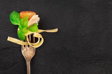 Italian pasta design. A closeup of a fork with pappardelle, basil, Parmesan cheese, tomato, and pepper, shot from above on a dark background with a place for text