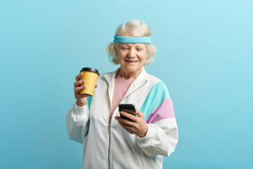 Mature female jogger taking a rest after morning running, holding cold drink in hands and looking at smart phone with cheerful look, reading positive news, isolated over blue background.