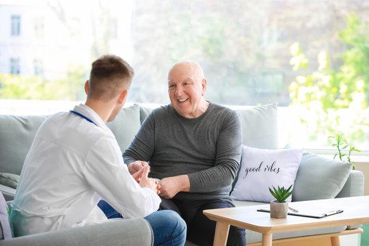 Doctor examining senior man in nursing home