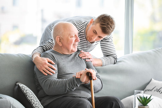 Male caregiver with senior man in nursing home