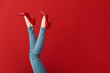 Legs of young woman in high-heeled shoes on color background Wall mural