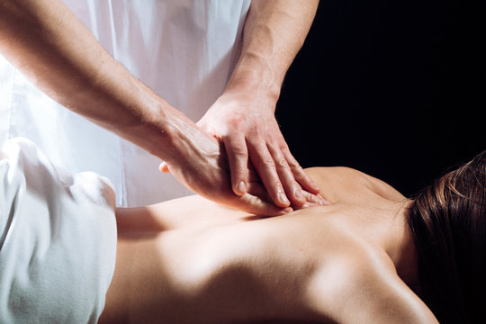 Masseur doing massage on woman body in the spa salon. Woman in spa salon, massage. Beauty treatment concept. Girl in spa gets a massages. Nude girl in masseur. Therapy, body care, massaging.