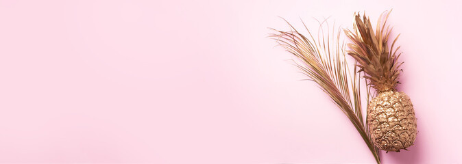 Creative layout. Gold pineapple and golden palm on pink background with copy space. Top view. Tropical flat lay. Exotic food concept, crazy trend Wall mural