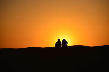 Silhouettes at sunset in the Arabian desert