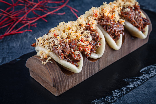 Close up on Gua bao, steamed buns with meat (veel). Bao served with tasty topping on dark background. Asian cuisine. Asian sandwich steamed gua bao. Japanese style fast food