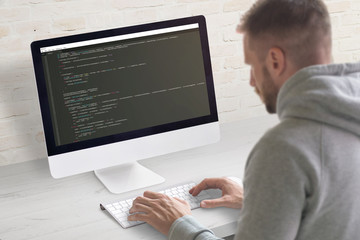 Wall Mural - Man coding app on a computer. Close-up scene. Clean office desk with brick wall in background.