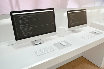 Wall Mural - Developer's office. Two computer displays with code editors.