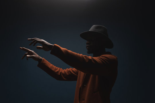 Portrait of male singer in hat and coat. Artist, performer