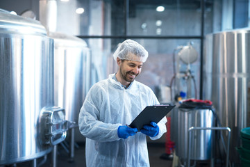 Industrial worker technologist in white suit with hairnet and protective gloves looking at checklist and smiling. Plant worker checking production in food industry.