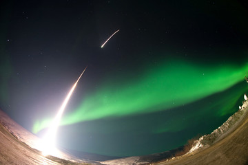 Rocket launch and aurora. Elements of this image furnished by NASA.
