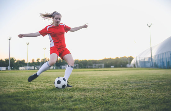 Close up of female soccer player kicking the ball at the goal