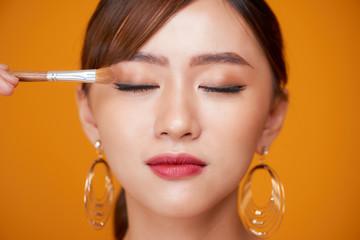 makeup artist deals makeup brush for eyes. makeup for a young beautiful girl