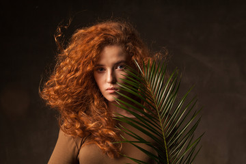 Energizer beautiful young curly ginger hair woman with green tropical plant palm branch posed in dark walls studio. Copy space background.