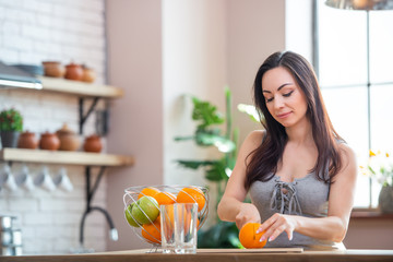 sporty young woman is cutting fresh orange for fruit juice in the kitchen. Horizontal indoors shot