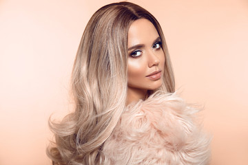 Spoed Foto op Canvas Kapsalon Ombre blond hairstyle. Beauty fashion blonde portrait. Sexy woman wears in pink fur coat. Beautiful girl model with makeup, long healthy hair style posing isolated on studio beige background.