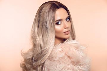 Ombre blond hairstyle. Beauty fashion blonde portrait. Sexy woman wears in pink fur coat. Beautiful...