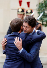 French President Emmanuel Macron accompanies Canadian Prime Minister Justin Trudeau after a meeting at the Elysee Palace in Paris