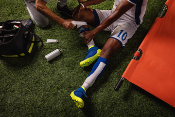 Soccer player injured knee during the game. Sport Doctors provide first aid to player on a professional football field. Close up