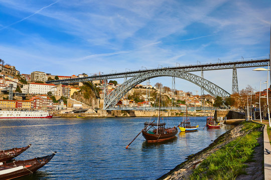 """Typical portuguese wooden boats, called """"barcos rabelos"""" transporting wine barrels on the river Douro with view on Villa Nova de Gaia  in Porto, Portugal"""
