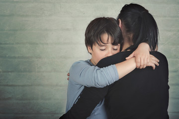 Sad child hugging his mother