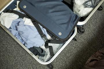 床においたスーツケース・衣服・出張