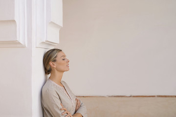 Natural beauty leaning against pillar in Moroccan villa in neutral tones