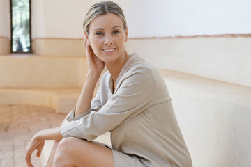 Stunning woman in soft neutral tones sitting in Moroccan villa smiling at camera