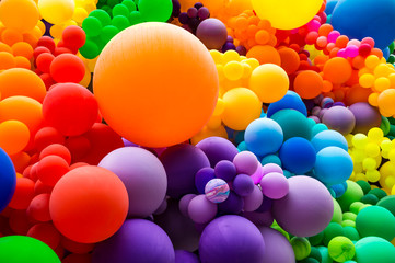 Jumble of rainbow colored balloons celebrating gay pride in a textured background