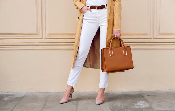 Closeup female legs. Woman in coat with bag. Fashion outfit