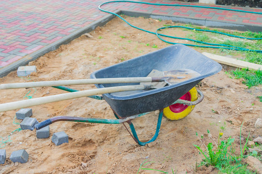 construction site with wheel barrow and spades.